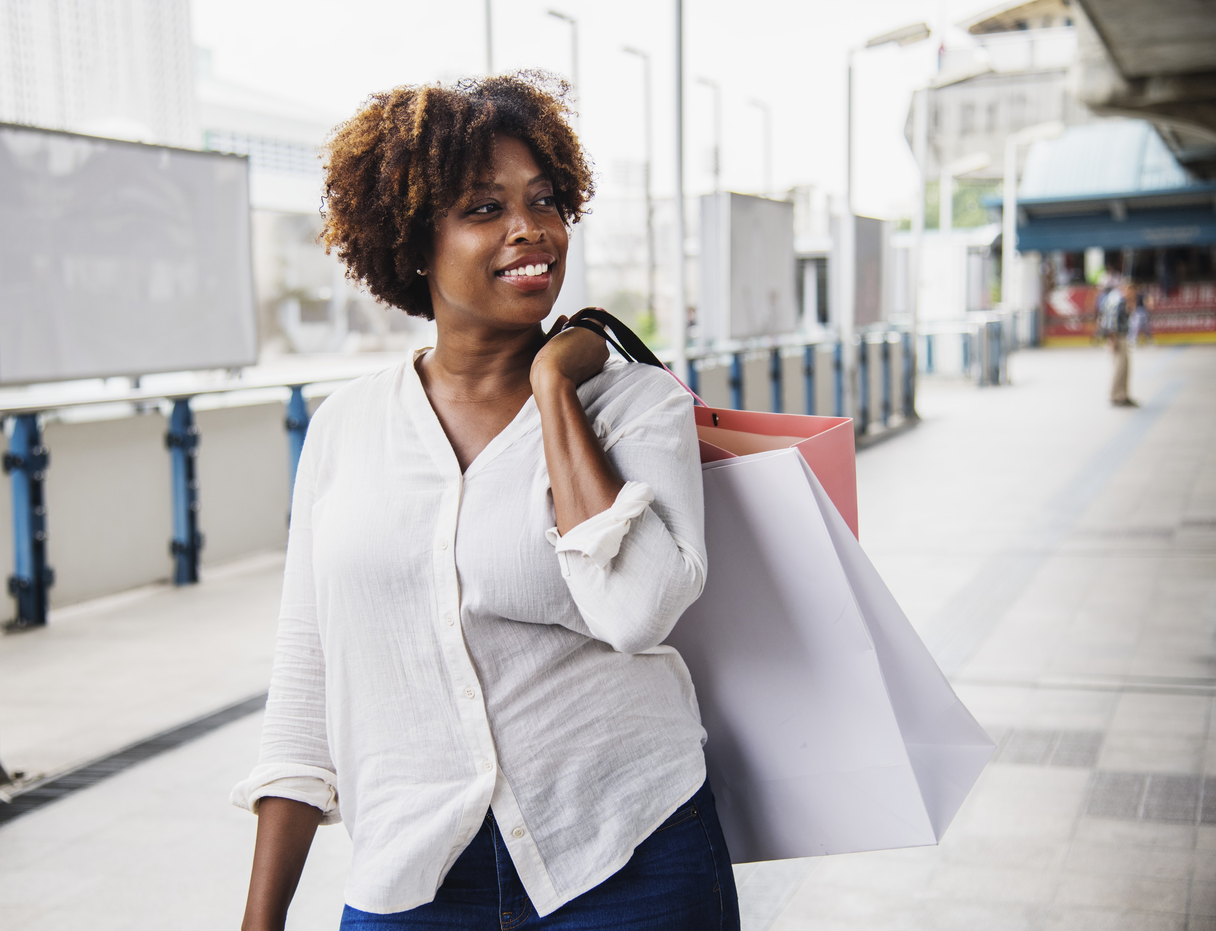 woman carrying paper bag walking on pathway
