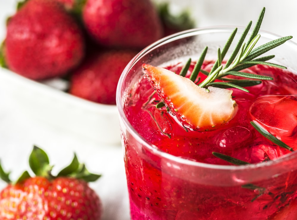 clear drinking glass with strawberry juice on white surface