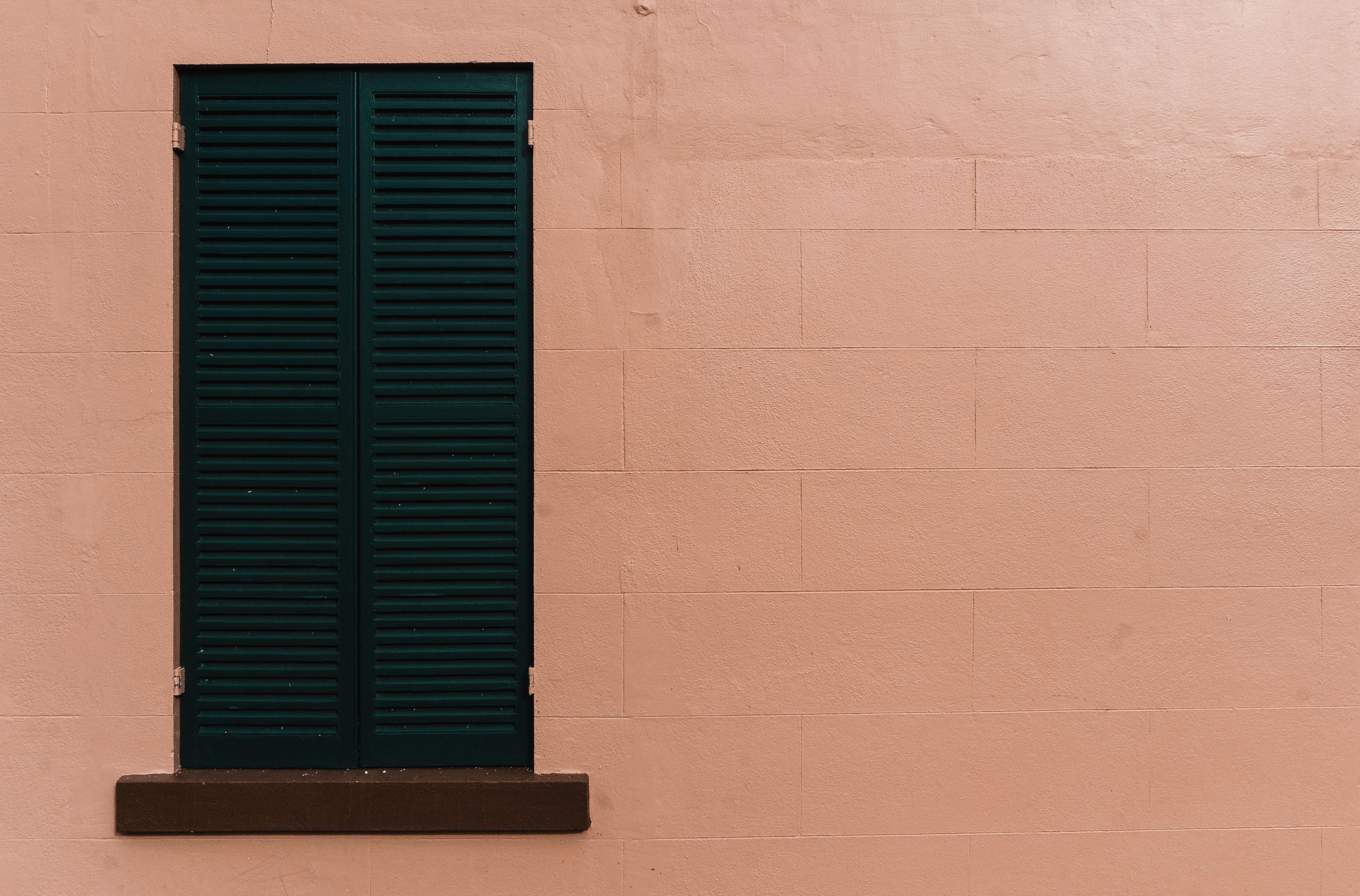 brown wooden building with green louvered window