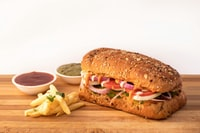 burger sandwich and potato fries on brown wooden surface