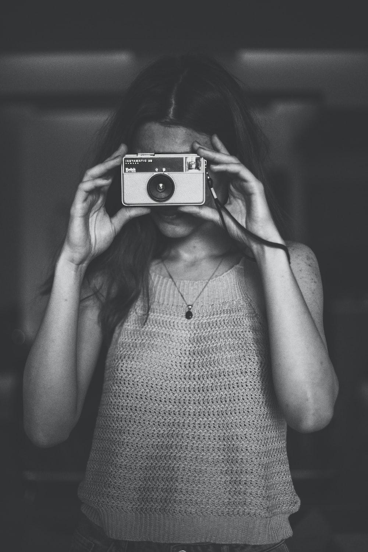grayscale photo of woman in spaghetti strap top using camera