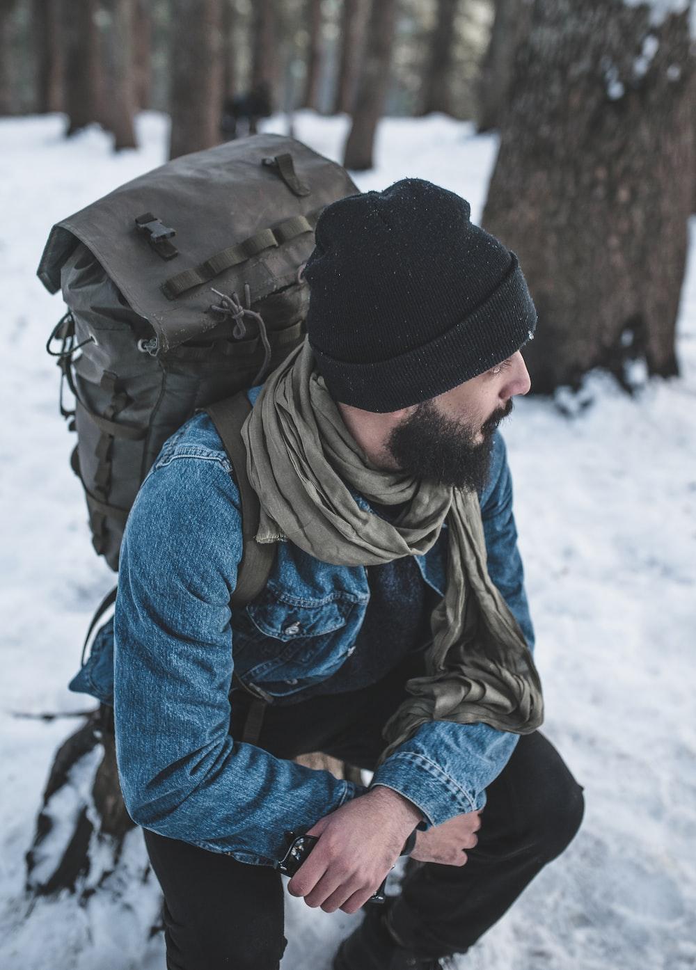 man sitting on snow near trees