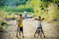 two boy riding on bicycle on dirt road