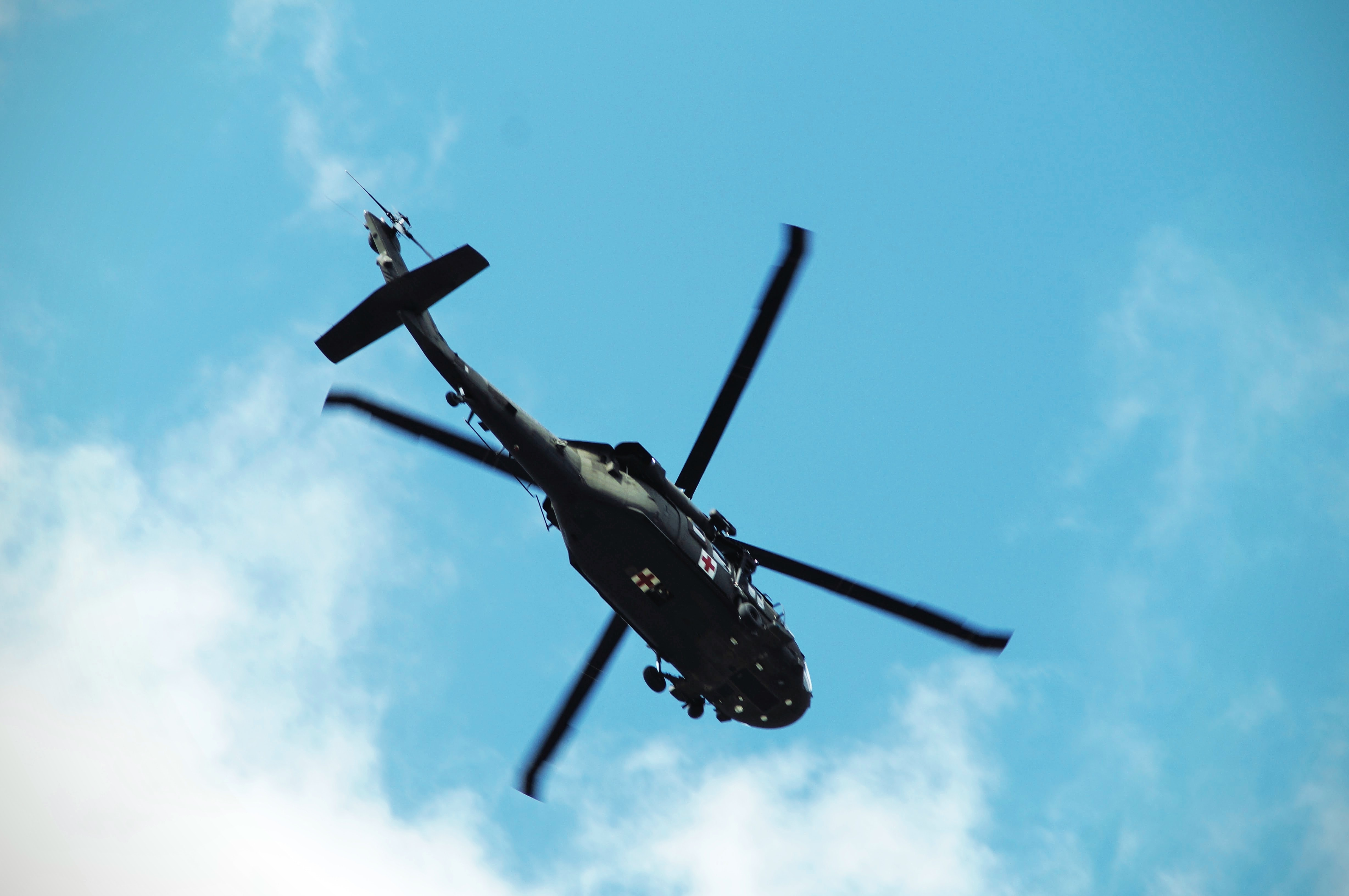 low angle photo of black and green helicopter