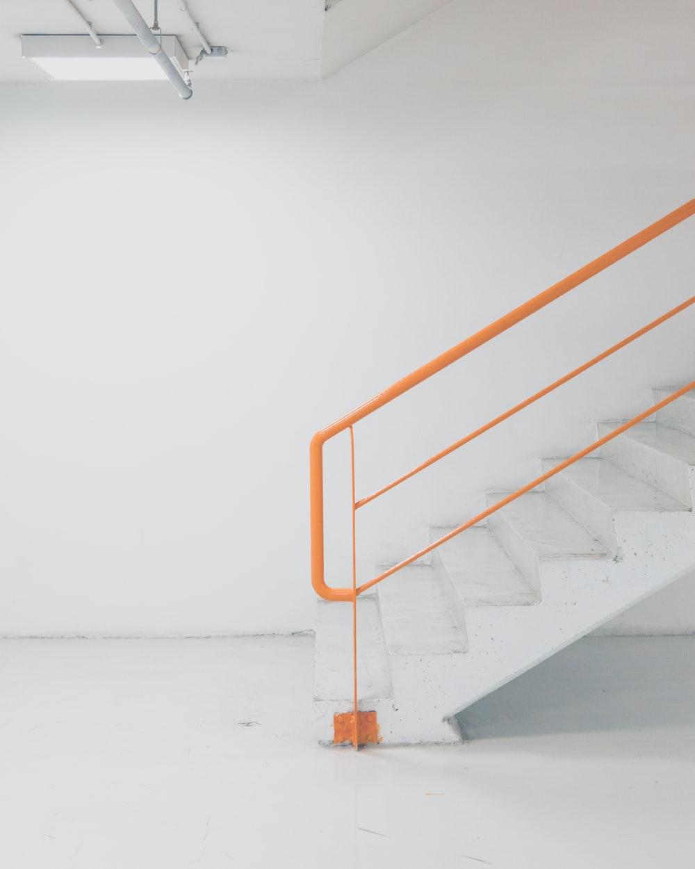 orange metal railing white concrete stairs