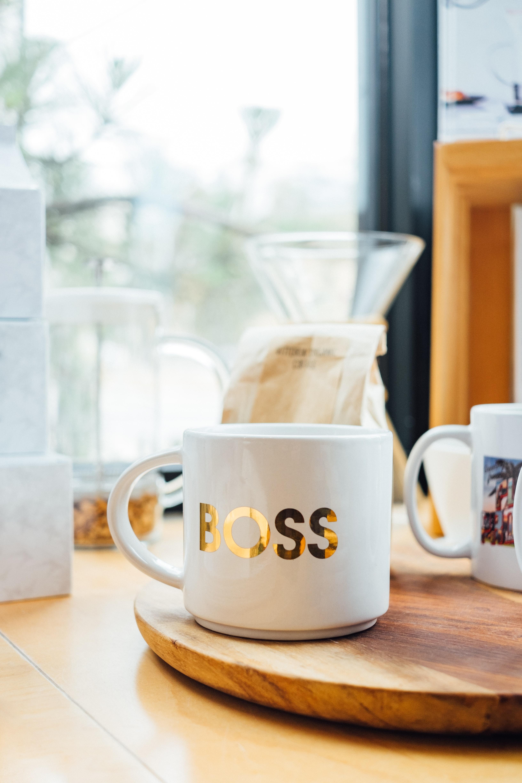 white Boss-printed ceramic mug on brown surface
