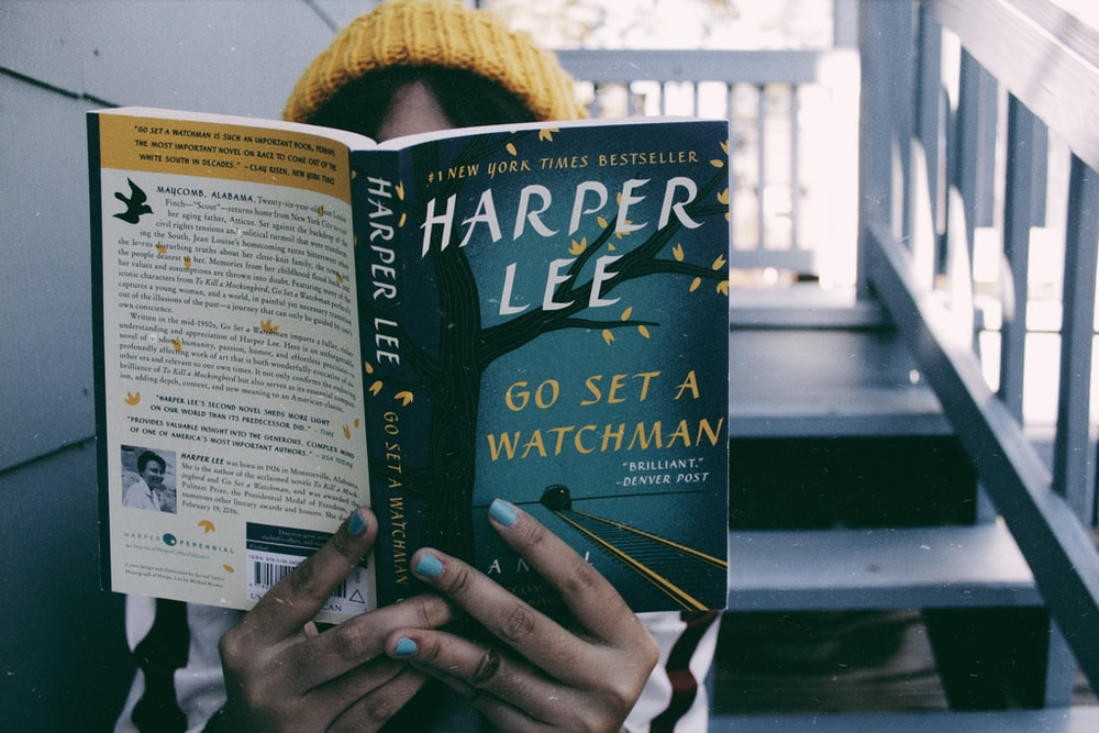 person sitting on stairs while reading Harper Lee book