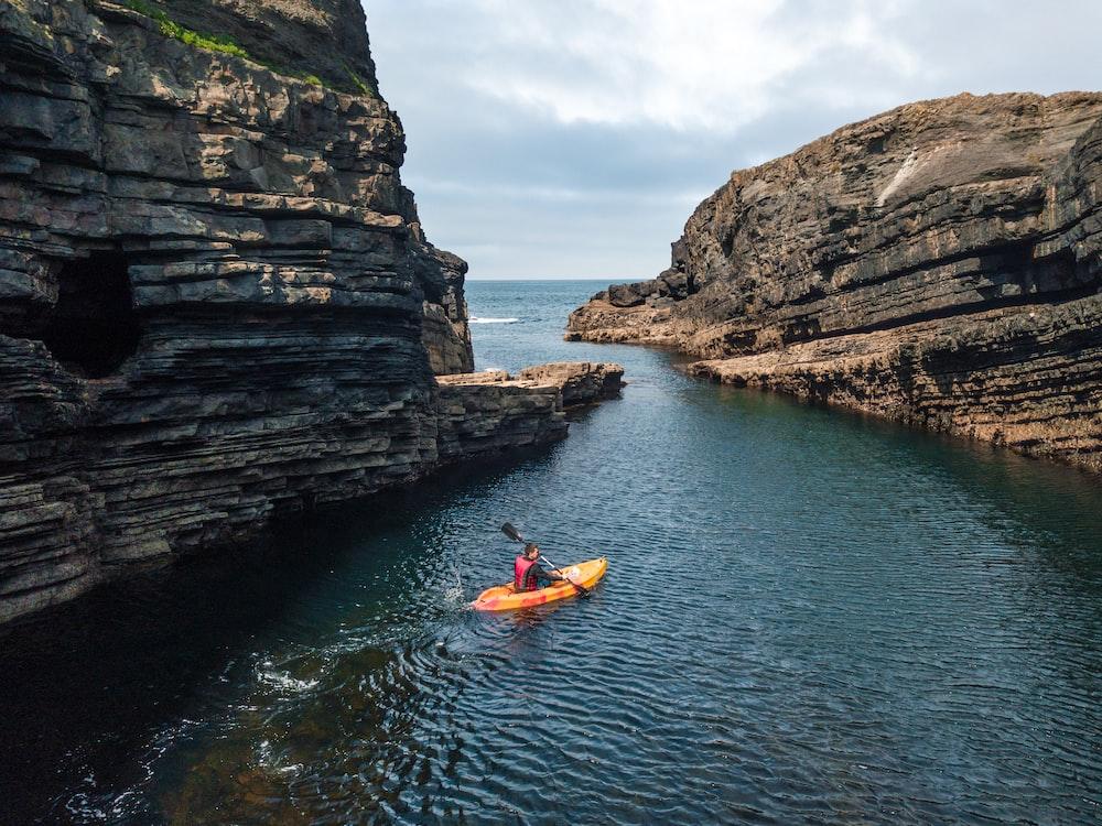 man riding kayak on body of water