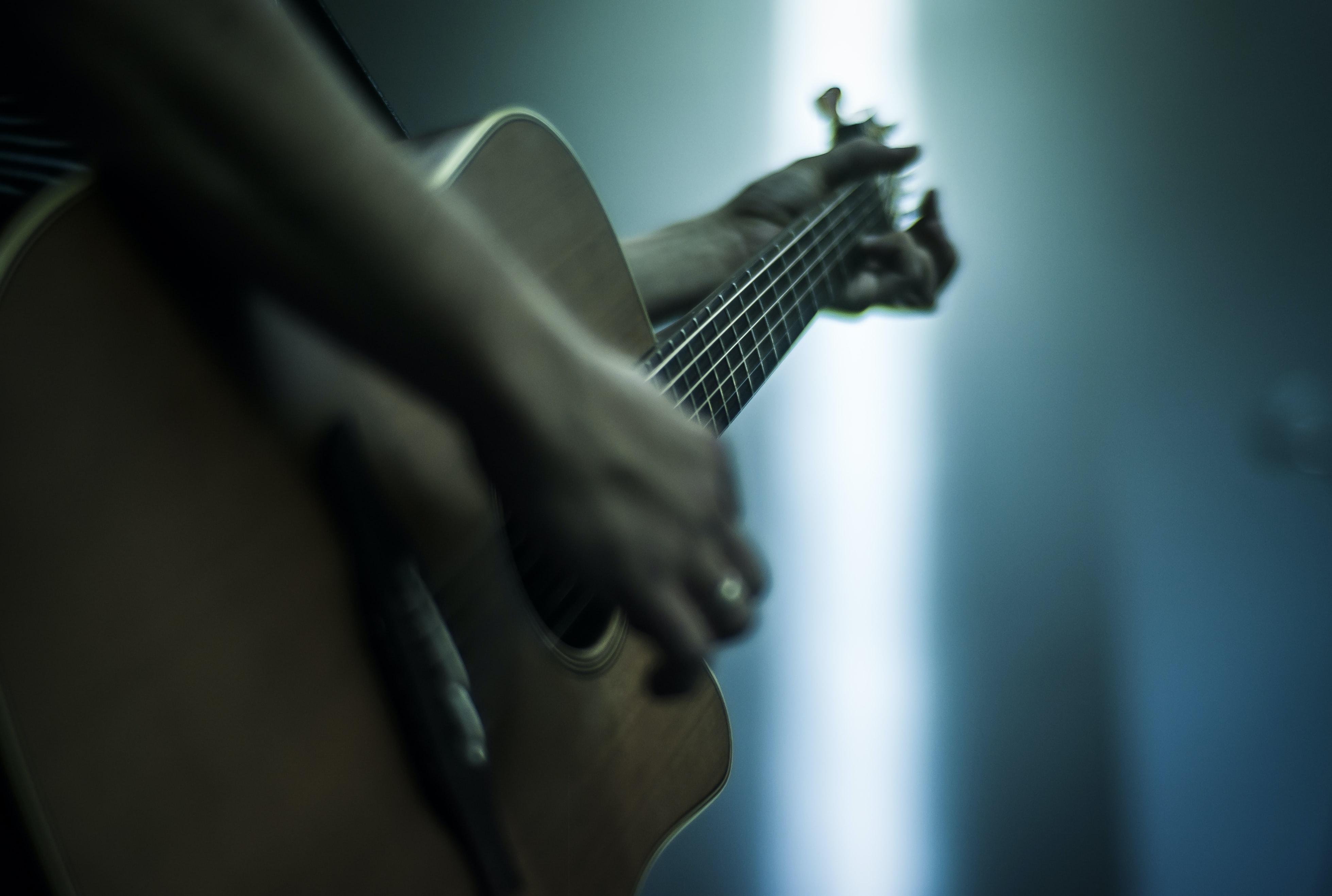 person playing acoustic guitar shallow focus photography