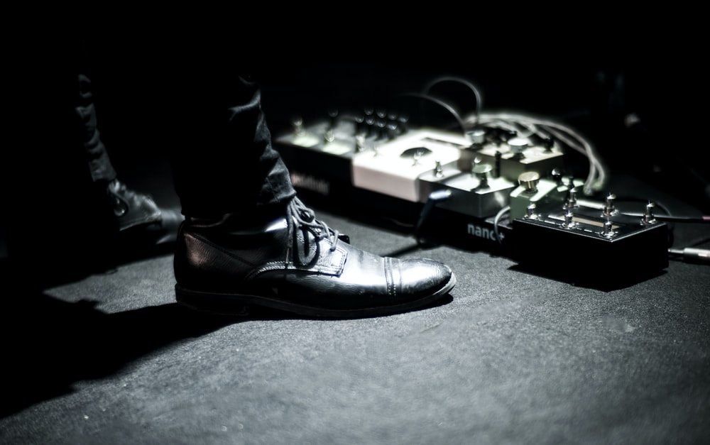 person's feet standing near effects pedals