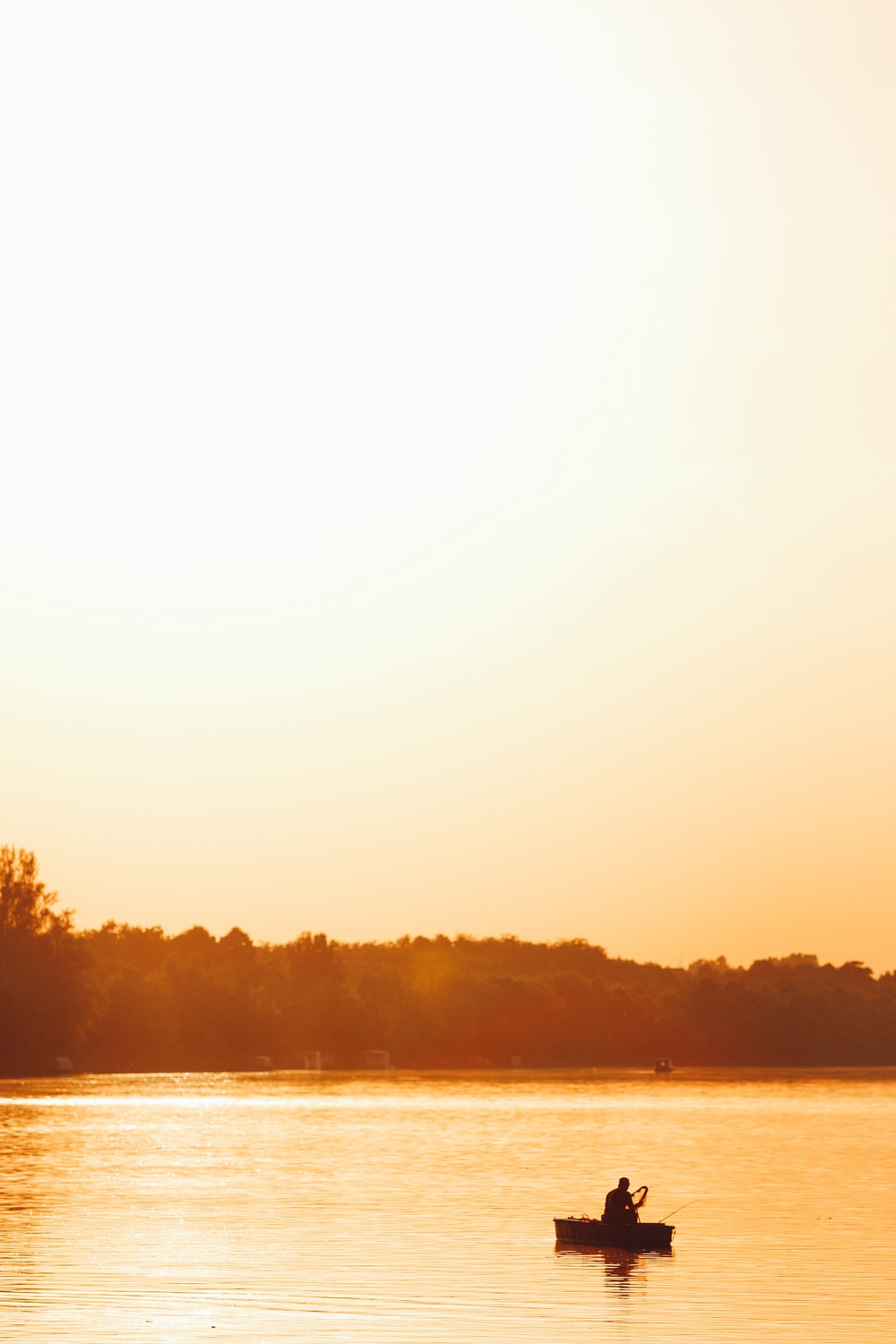 silhouette of person on boat at the center of the lake under clear sky