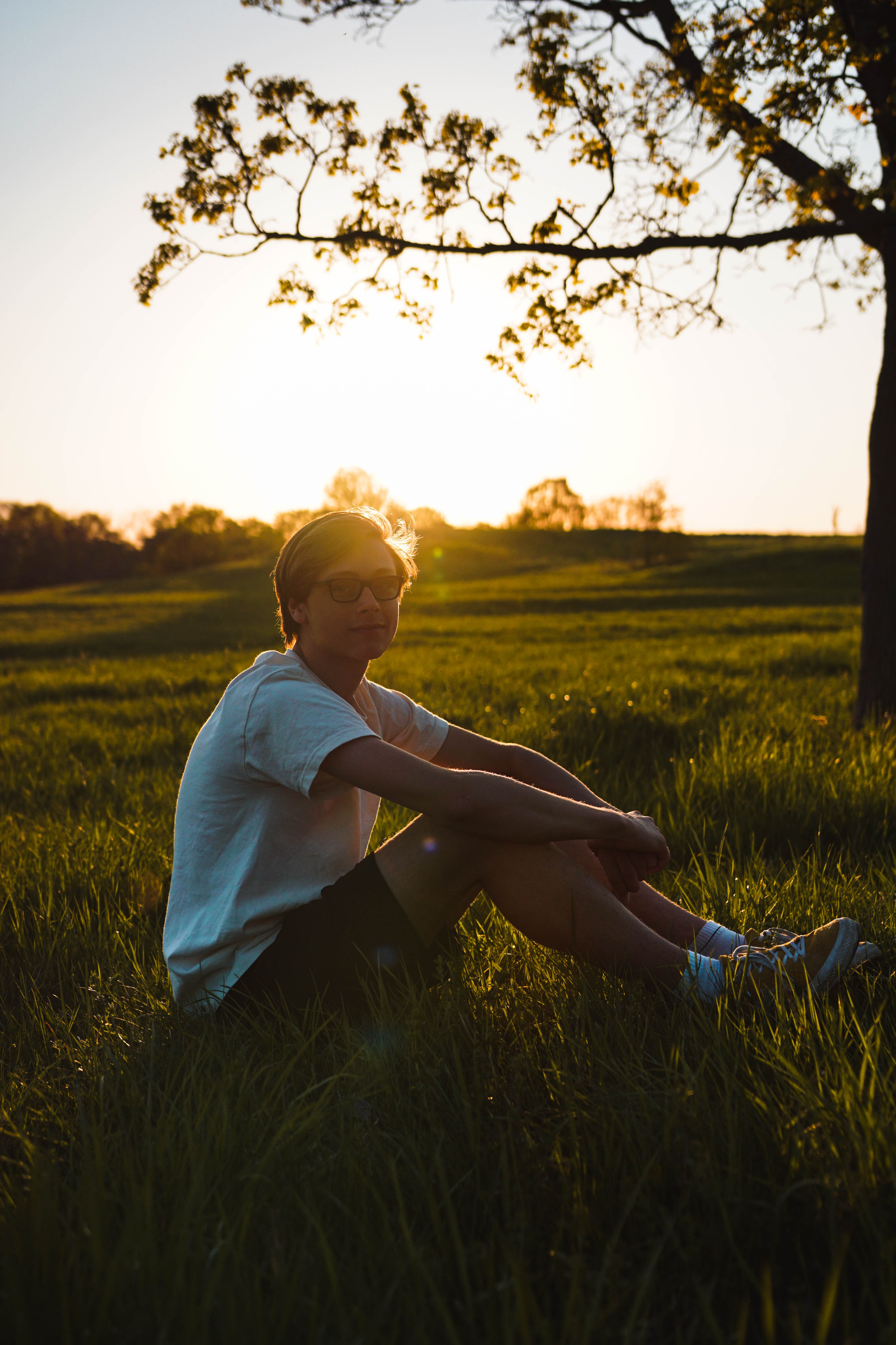 man sitting on grass while resting hand on knee during golden hour