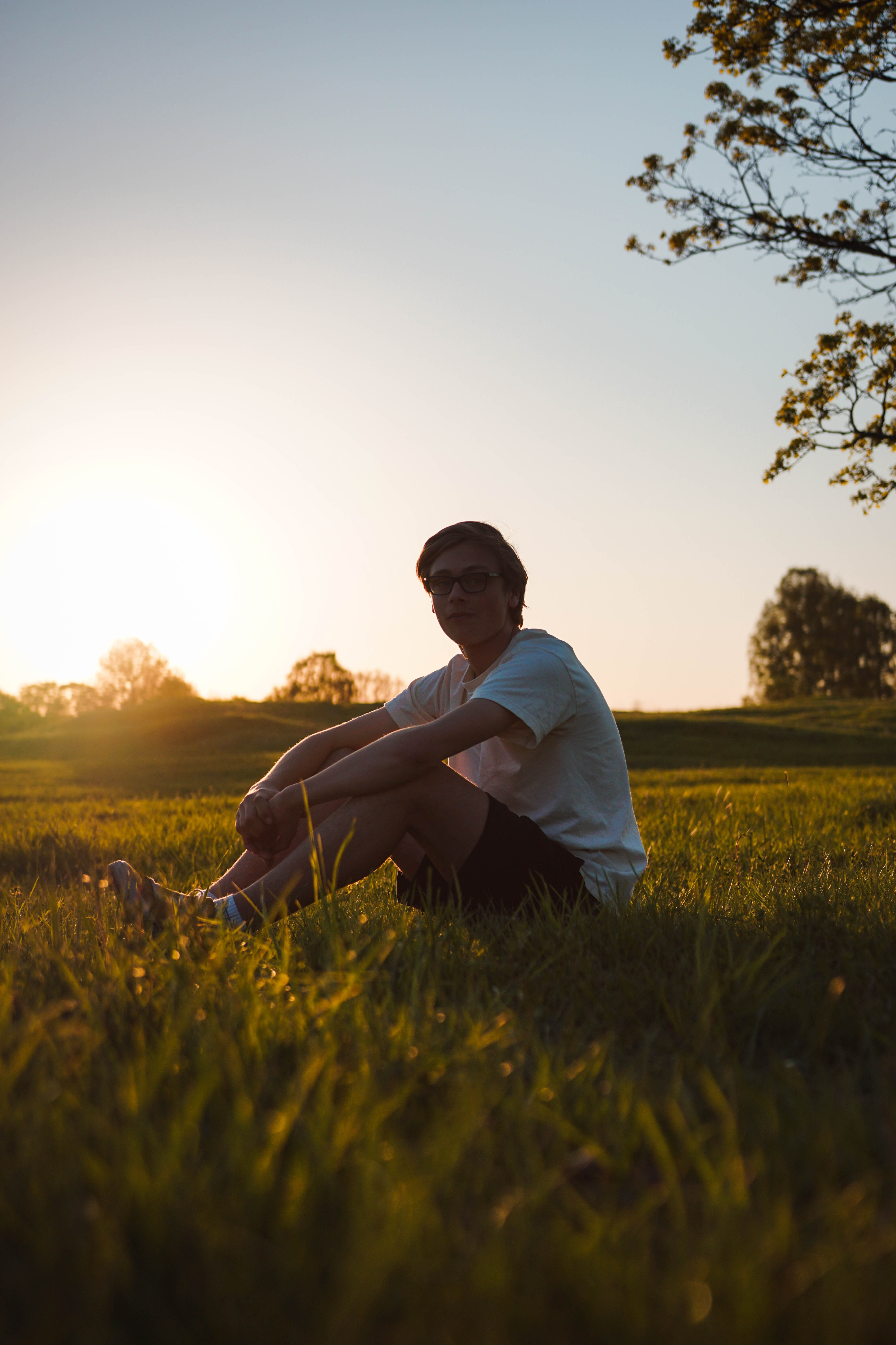man sitting on grass field during sunset