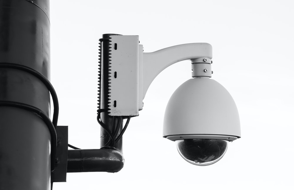 white security camera on post