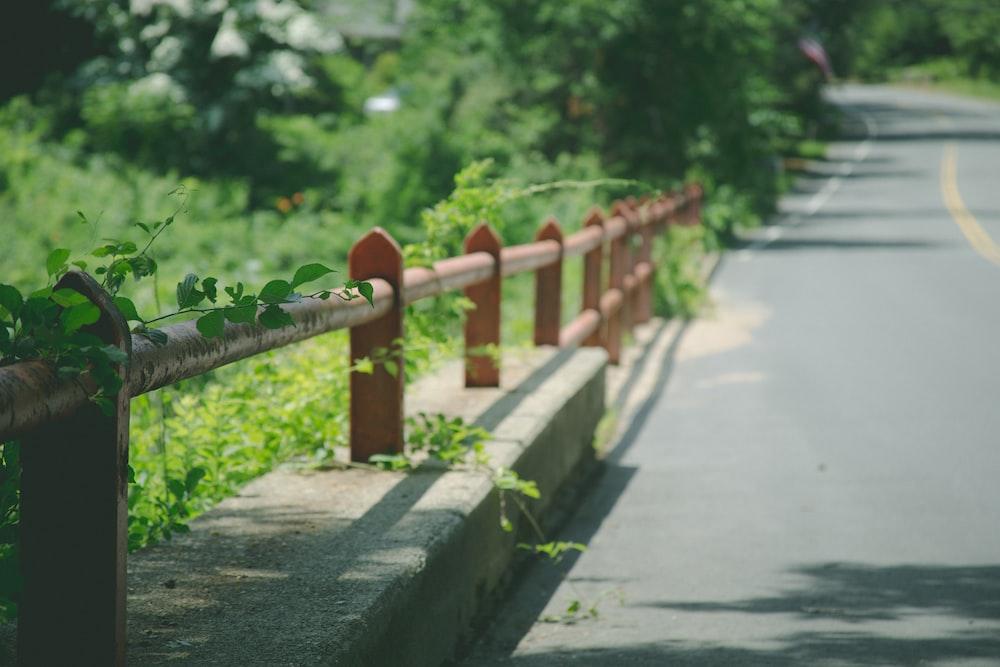 red metal railings on roadside at daytime