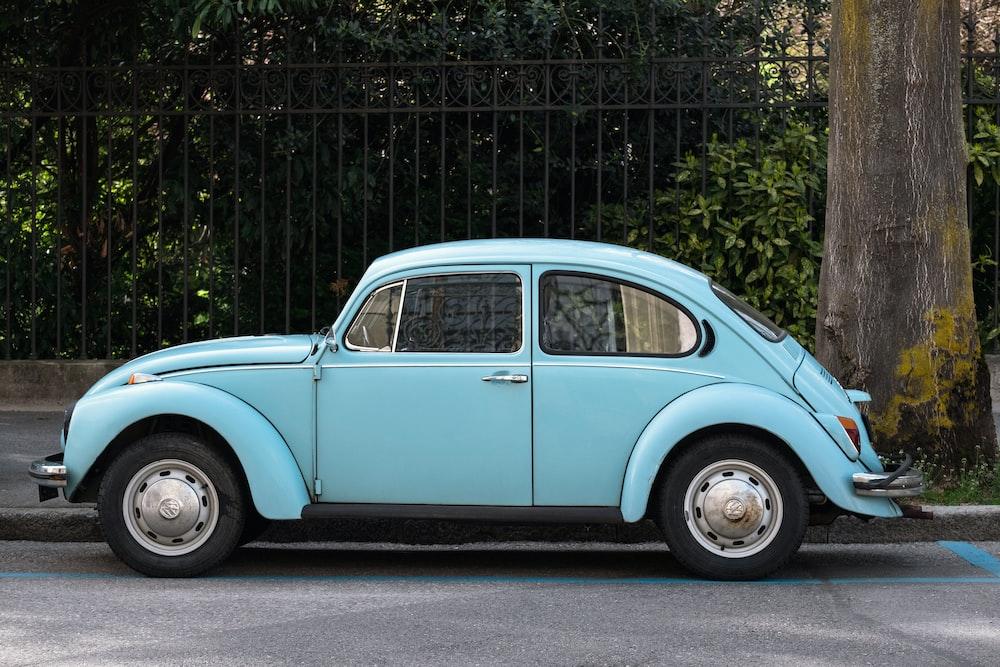 teal Volkswagen Beetle parked beside road
