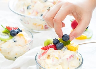 person holding blueberry fruit with hands on top of fruit salad