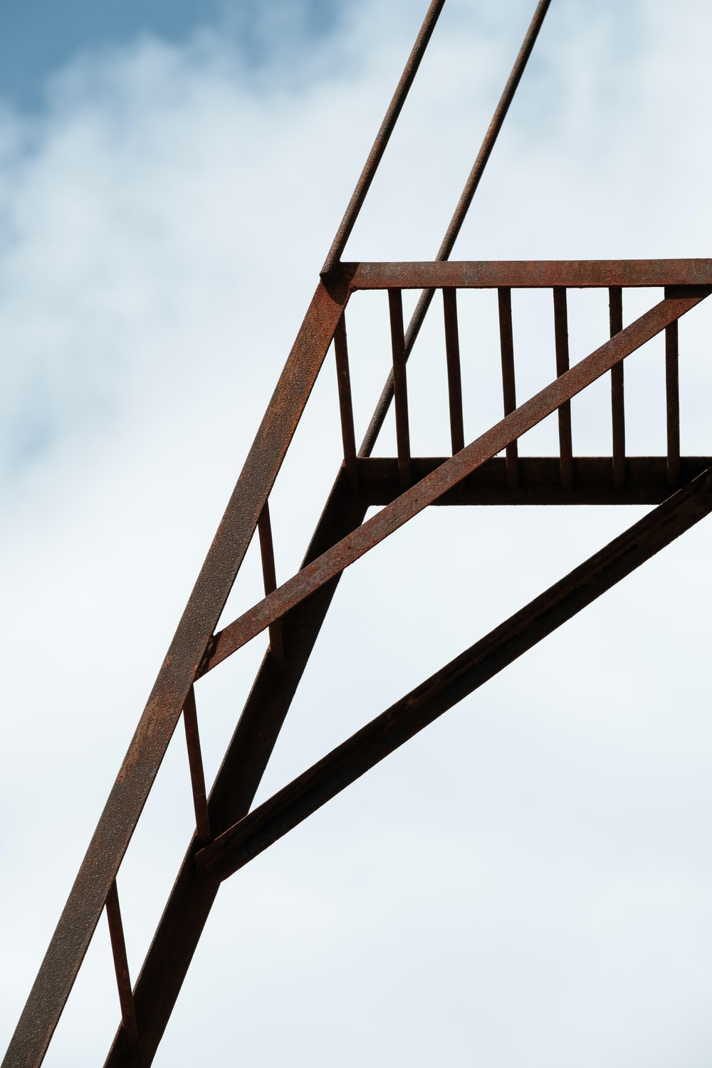 low angle photography gray metal stairs under white clouds