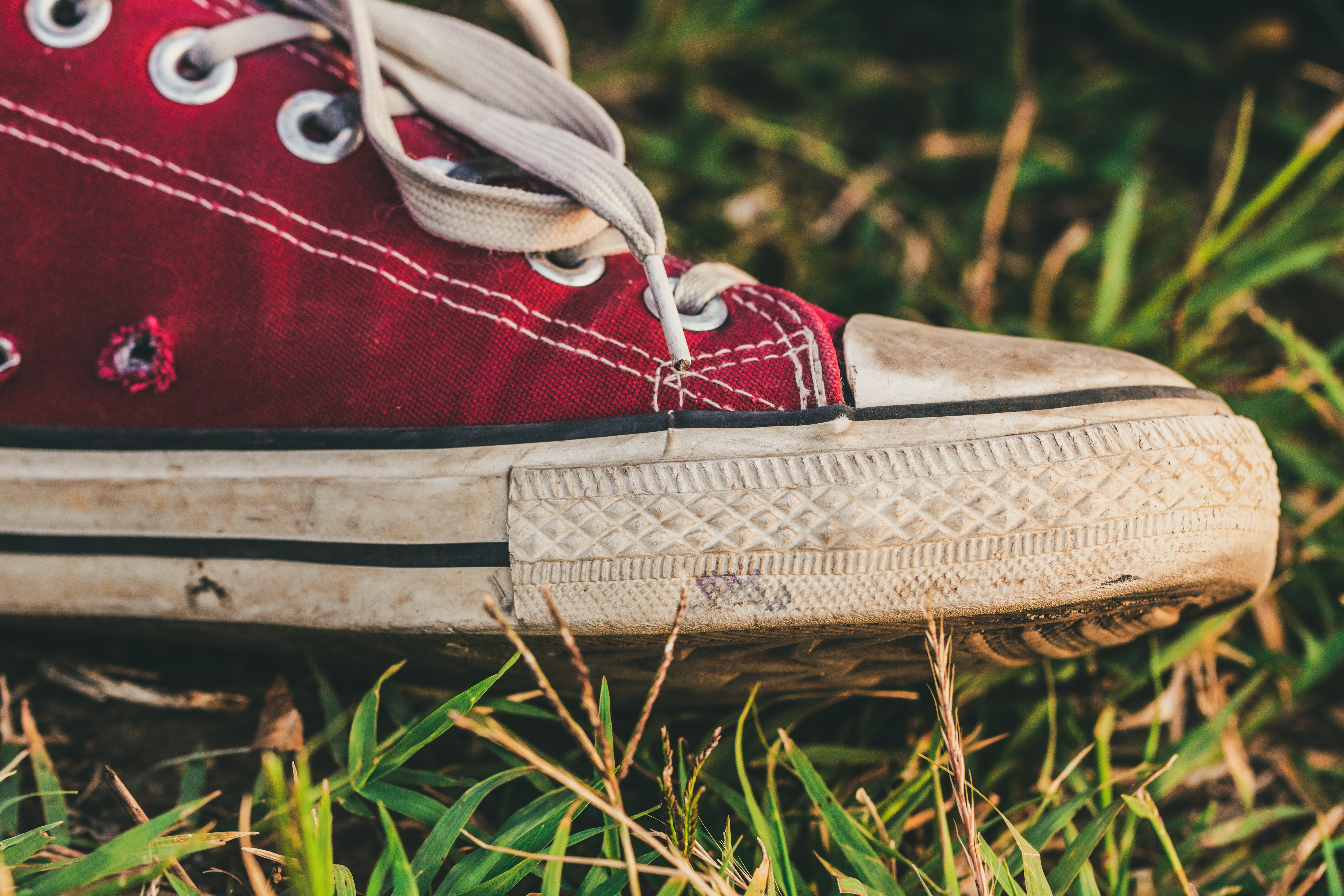 red and white shoe on grass