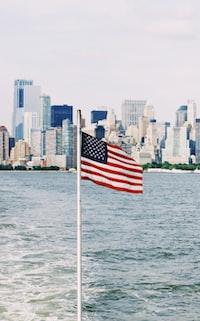 U.S.A. flag on pole near sea under cloudy sky