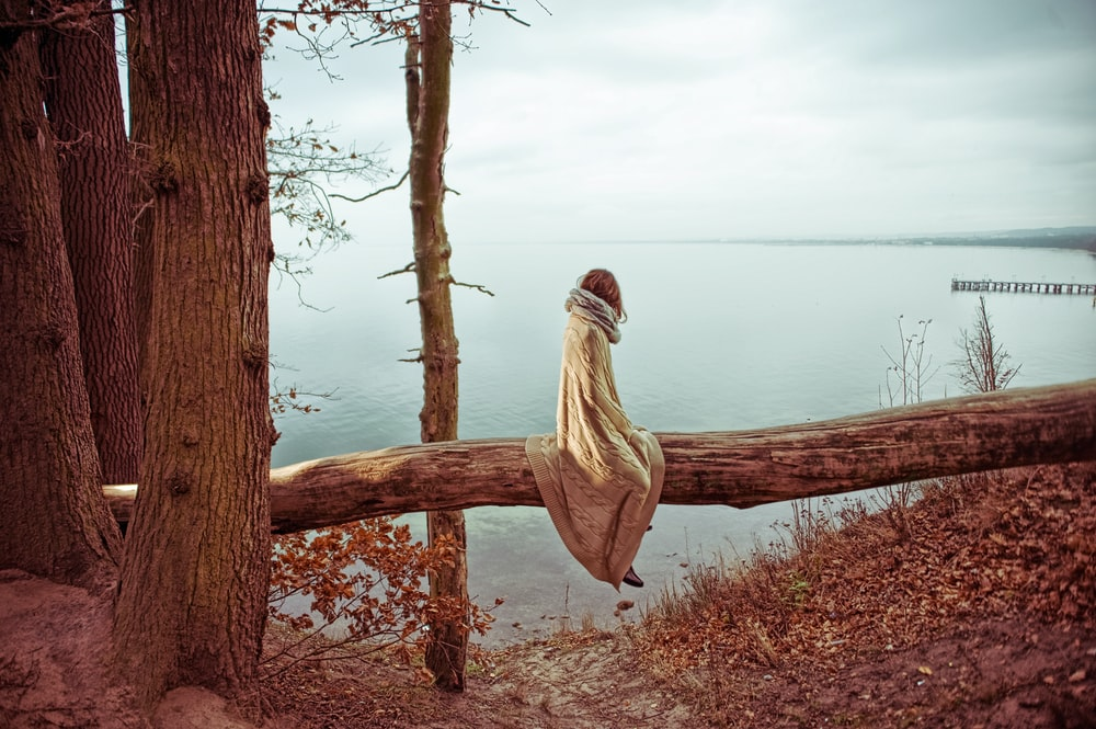 woman sitting on tree log facing at body of water