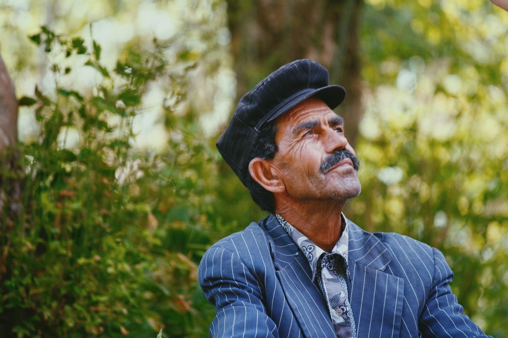 selective photo of man wearing blue shirt standing beside tree