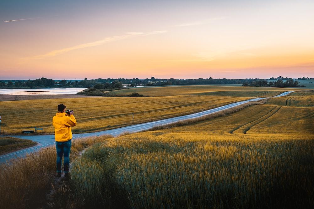 man taking photo of grassland