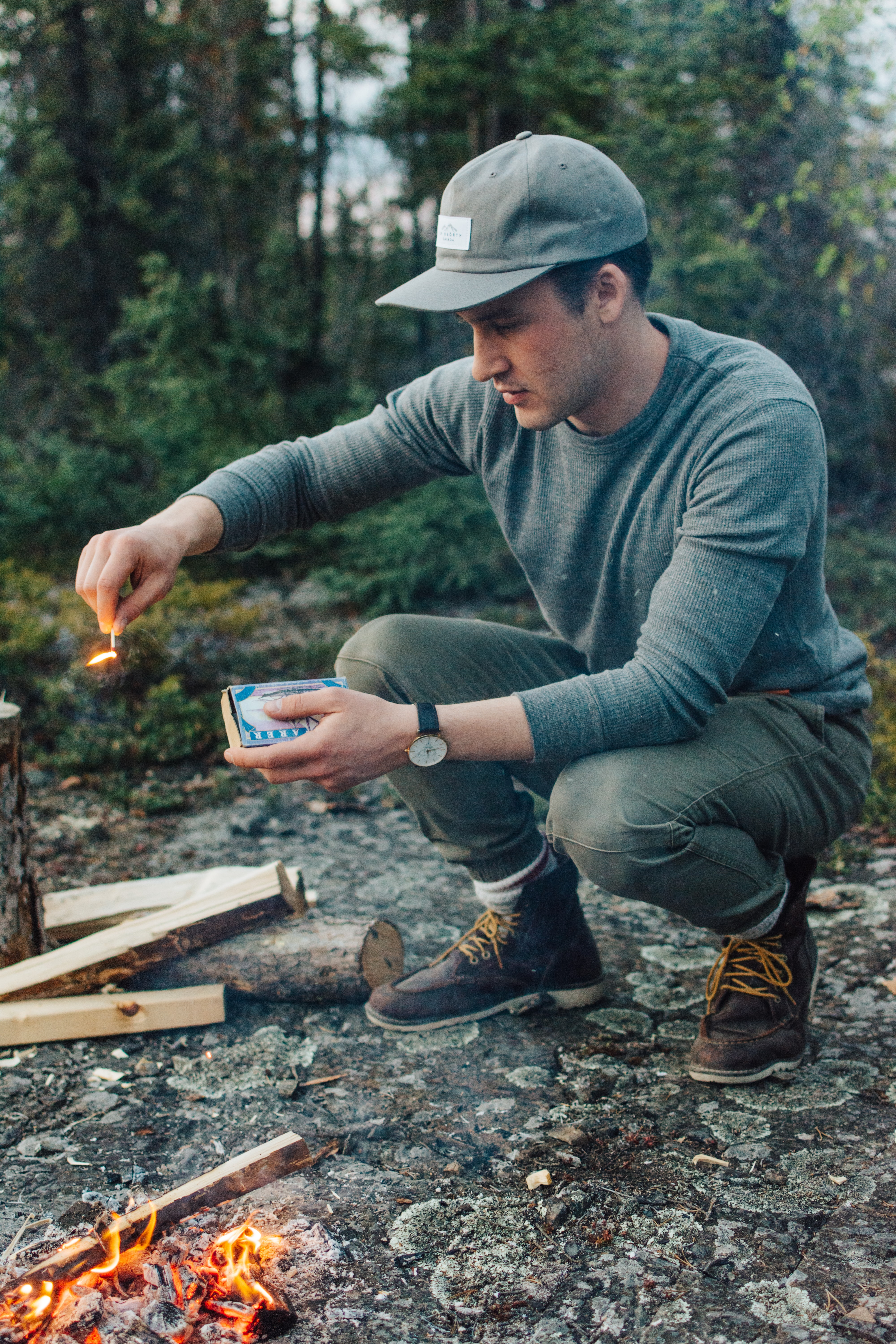 selective focus photography of man holding lit matchstick outdoors