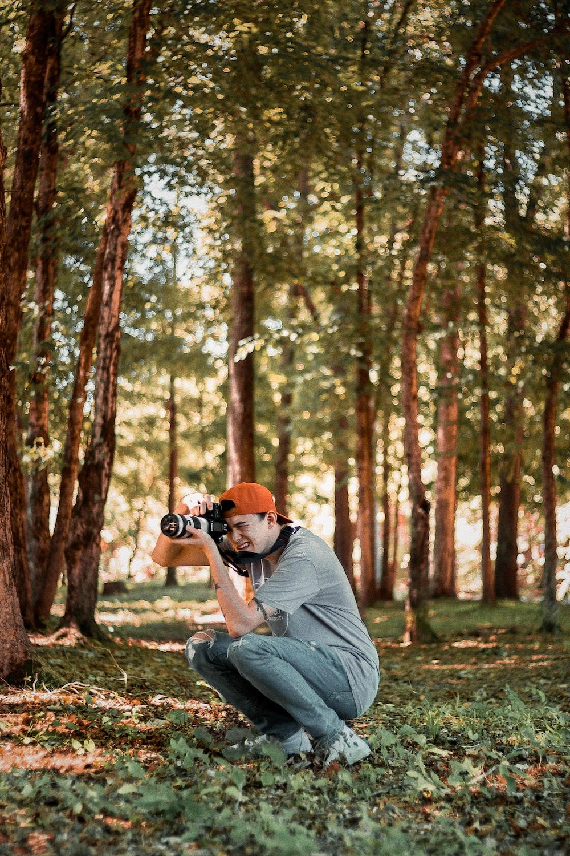man sitting while taking photo near tree