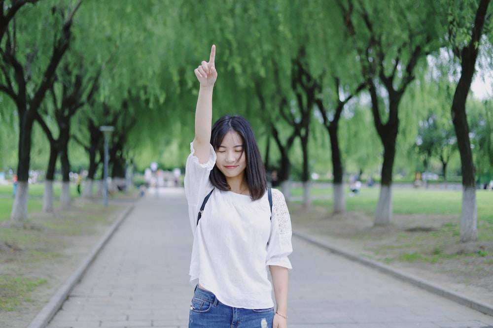 woman raising her right arm