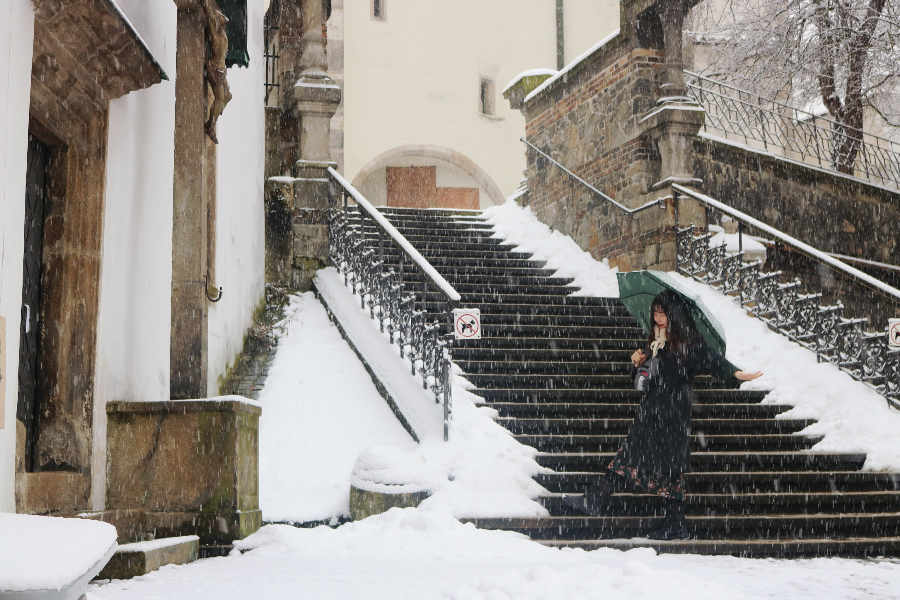 woman holding umbrella walking on stair