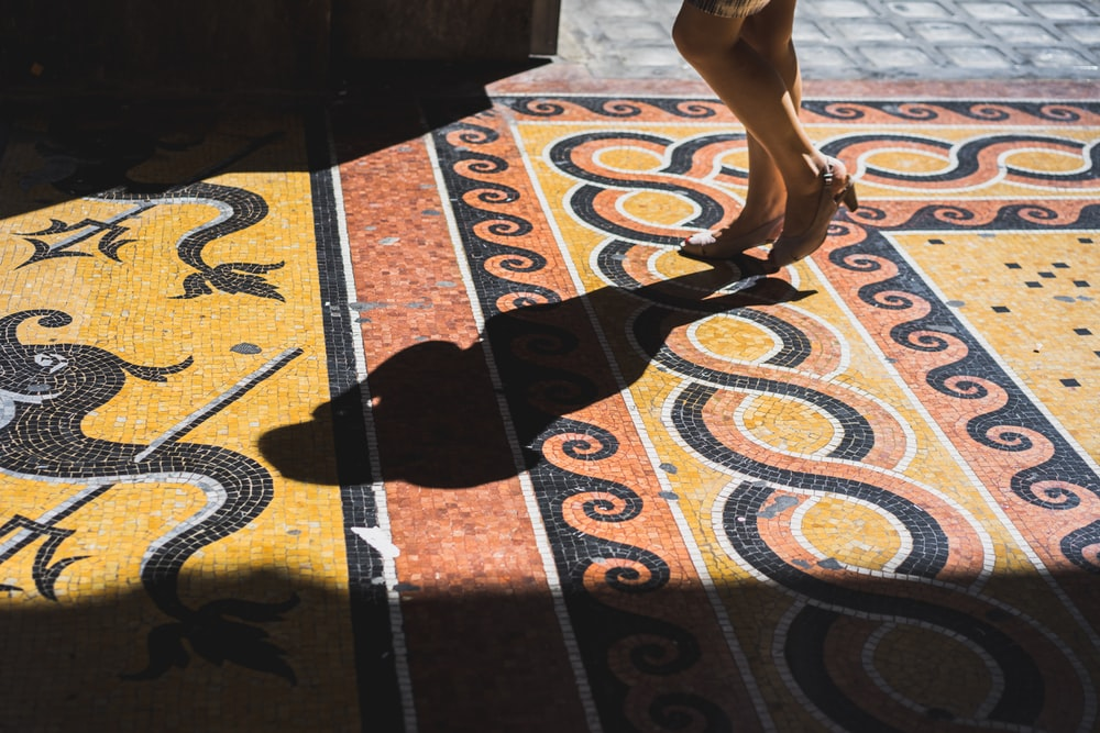 person standing on orange, yellow, and black tiled surface