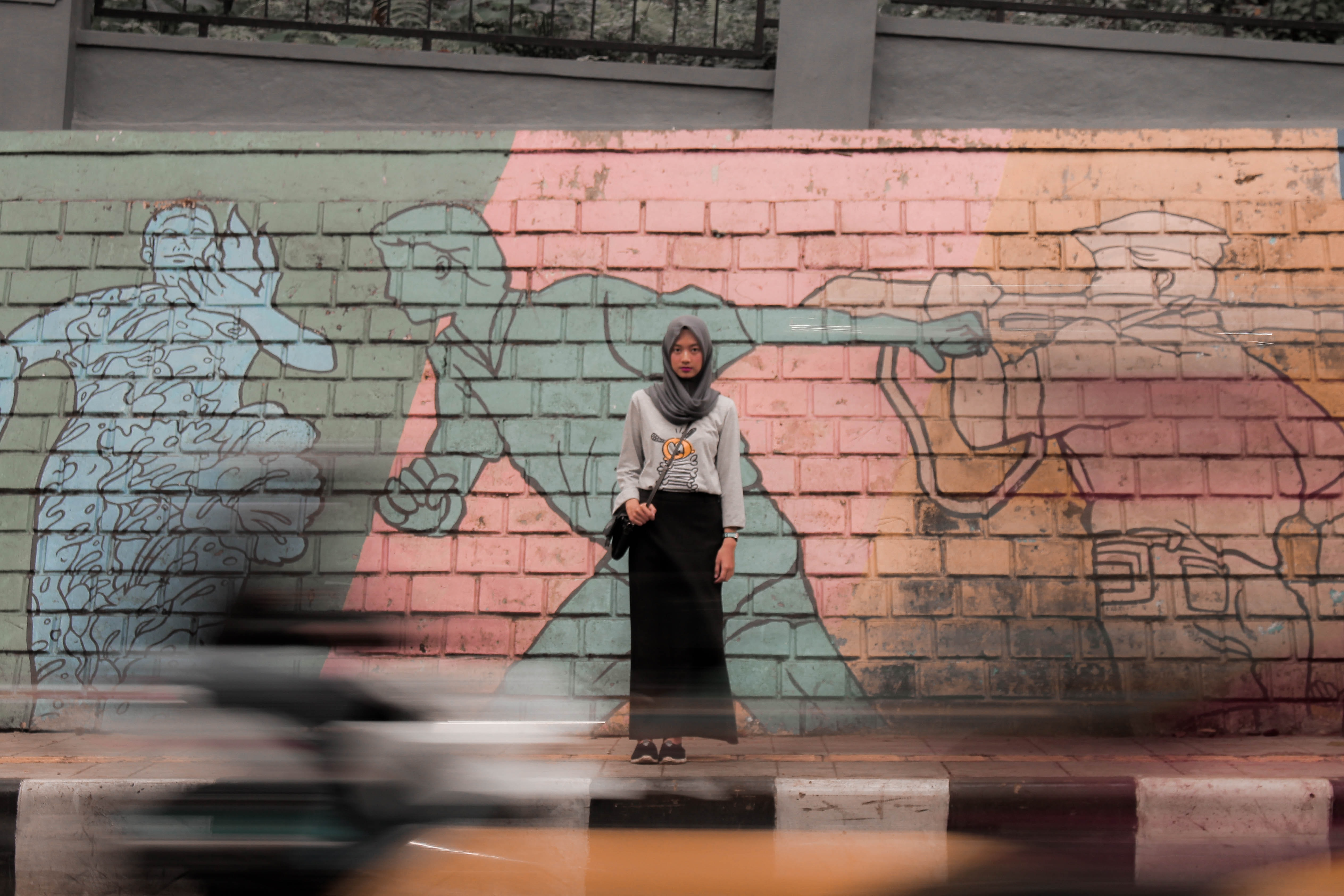 woman standing against mural wall