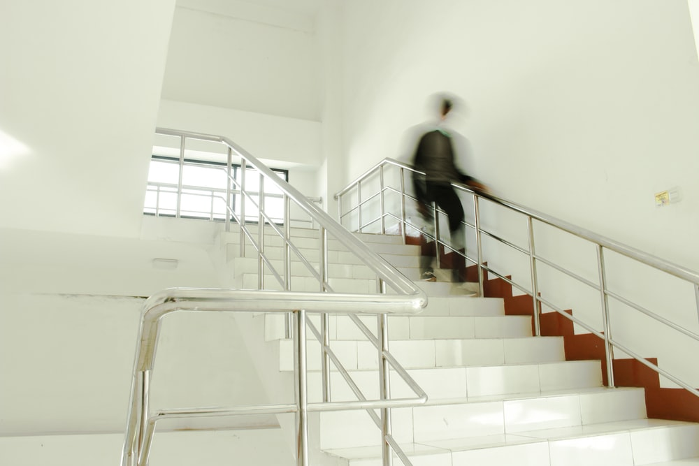 person going down white tiled stairs
