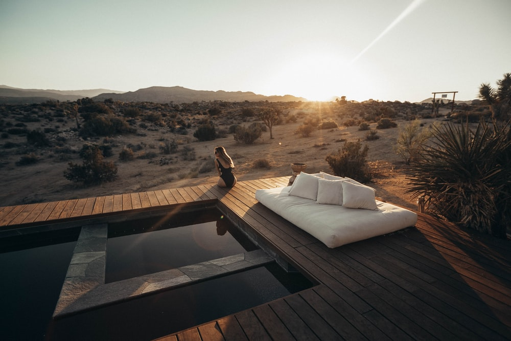 white mattress and pillows on wooden flooring near swimming pool