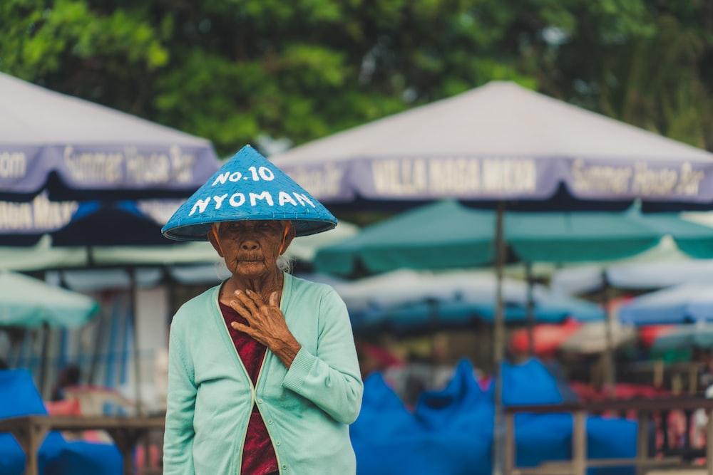 woman wearing blue hat near purple patio umbrellas