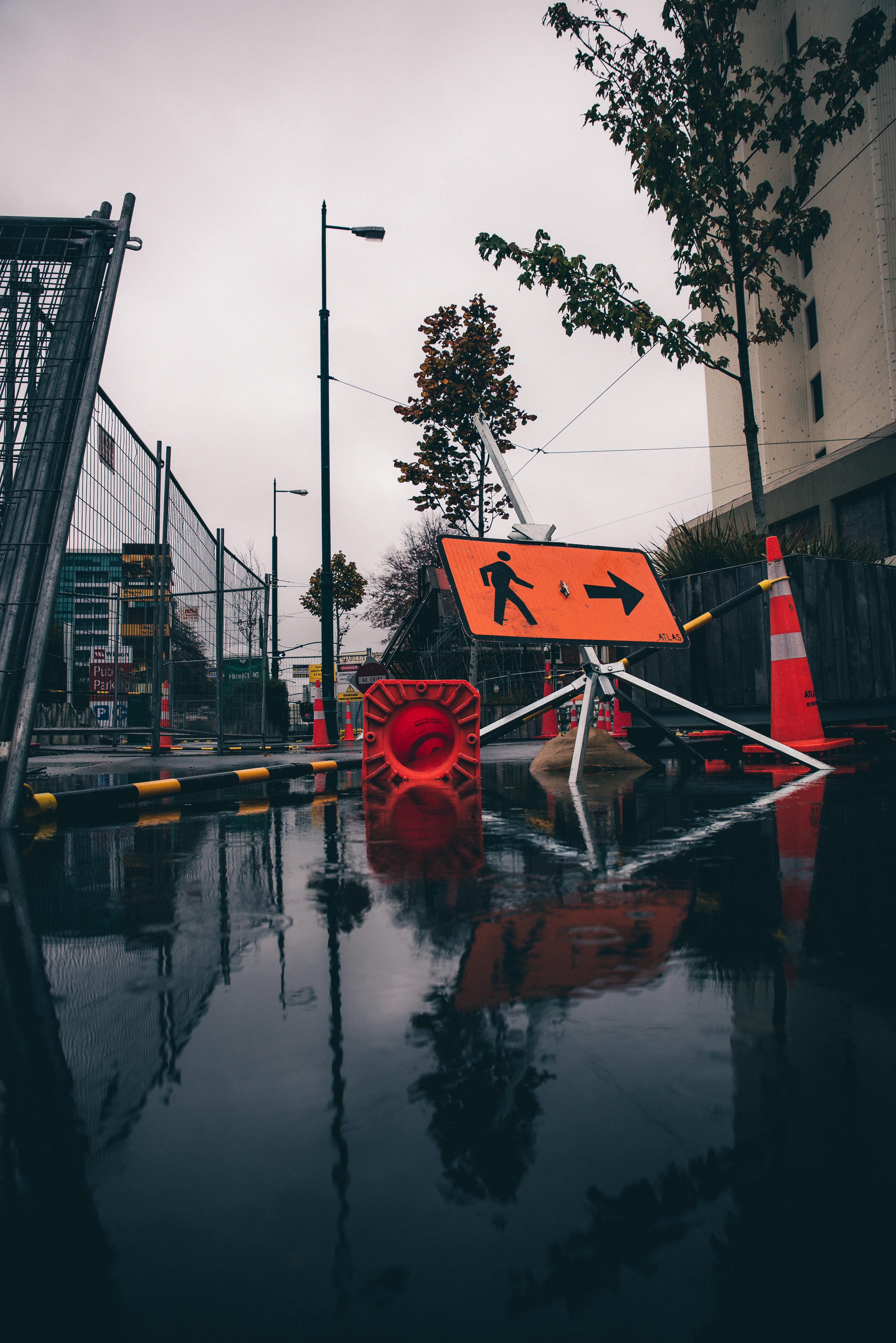 orange and white traffic cone near light post during daytime