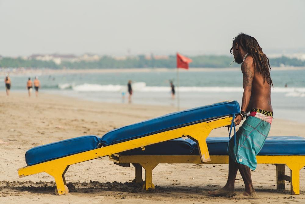 man carrying sunlounger chair