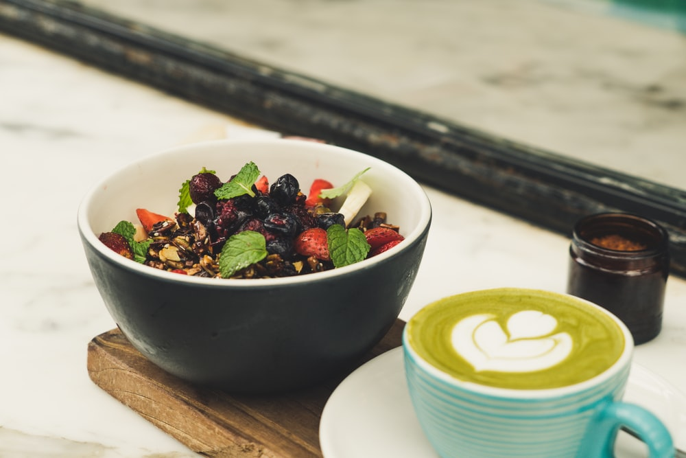berry salad in black ceramic bowl beside cappuccino coffee
