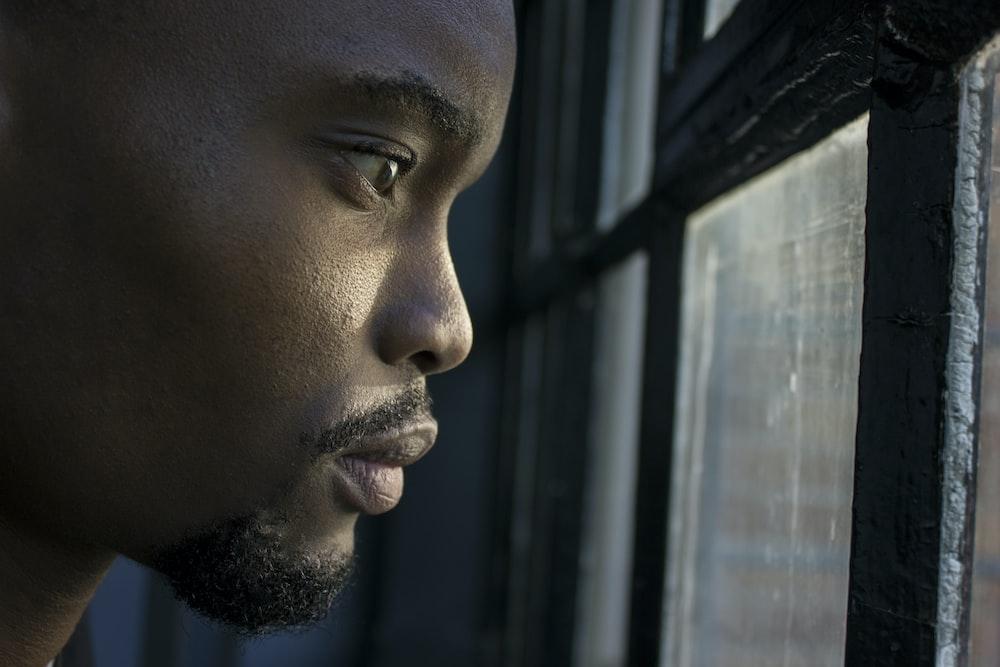 man near glass window pane