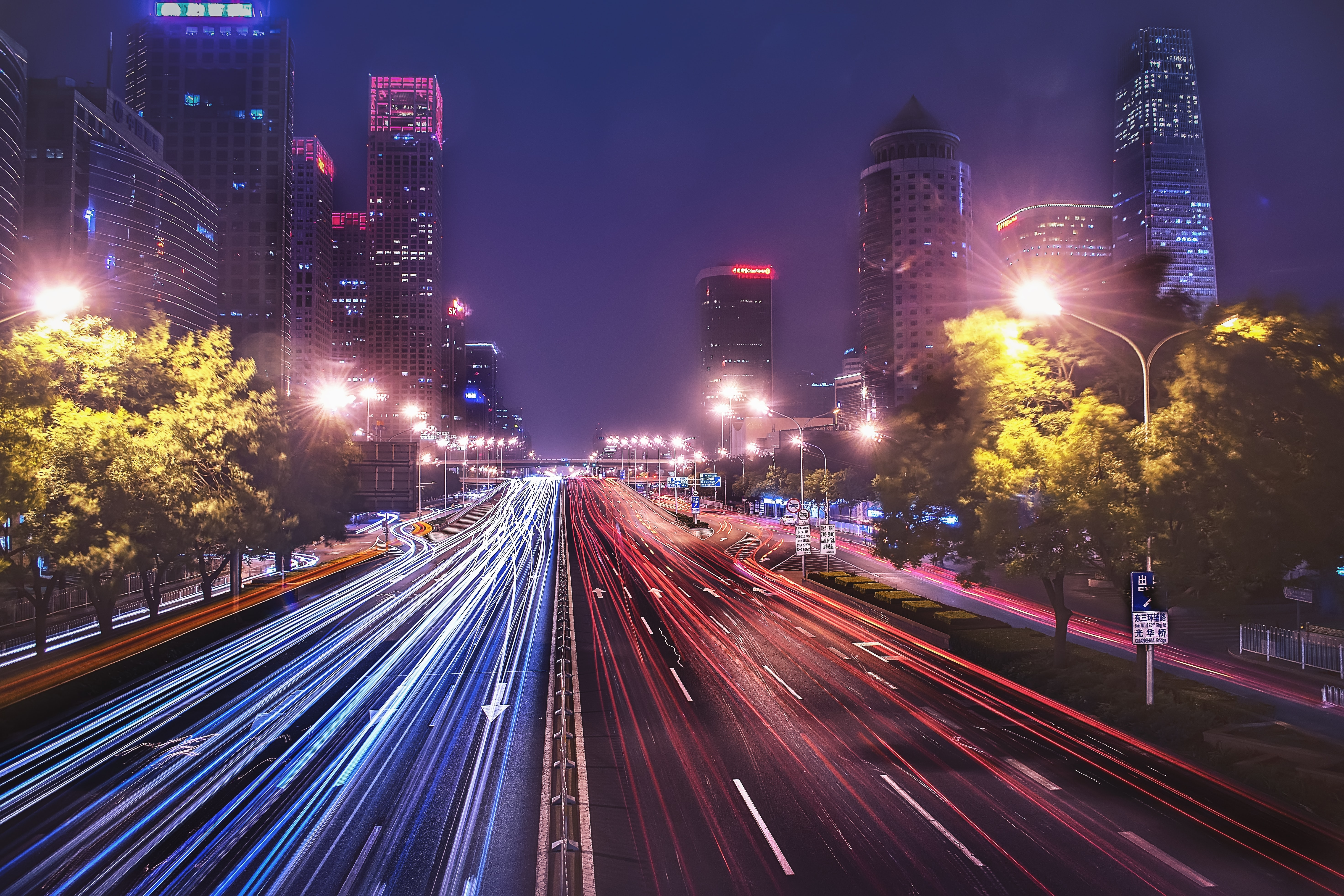time-lapse photography of cars passing on road between buildings
