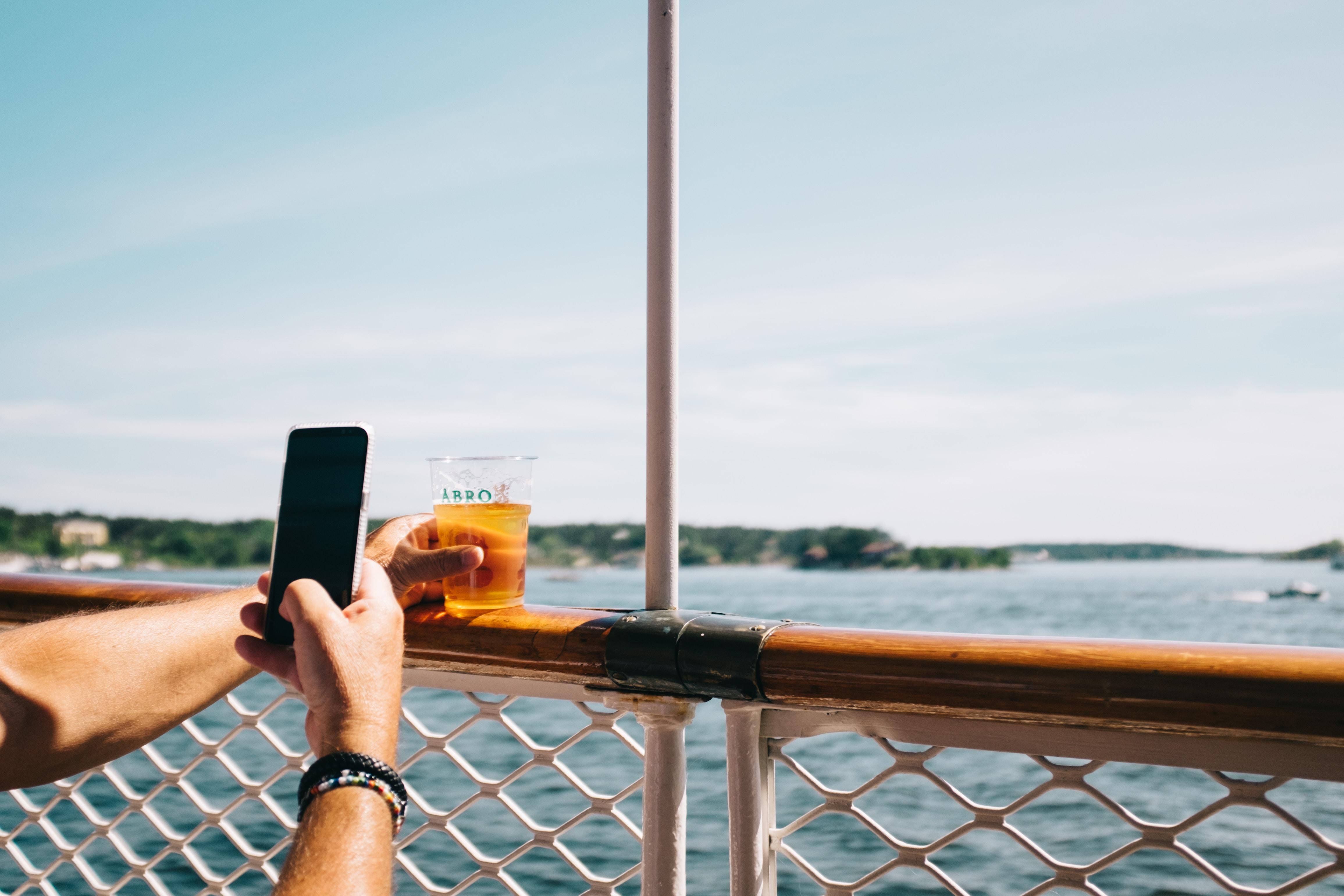 person taking photo of orange juice on rail