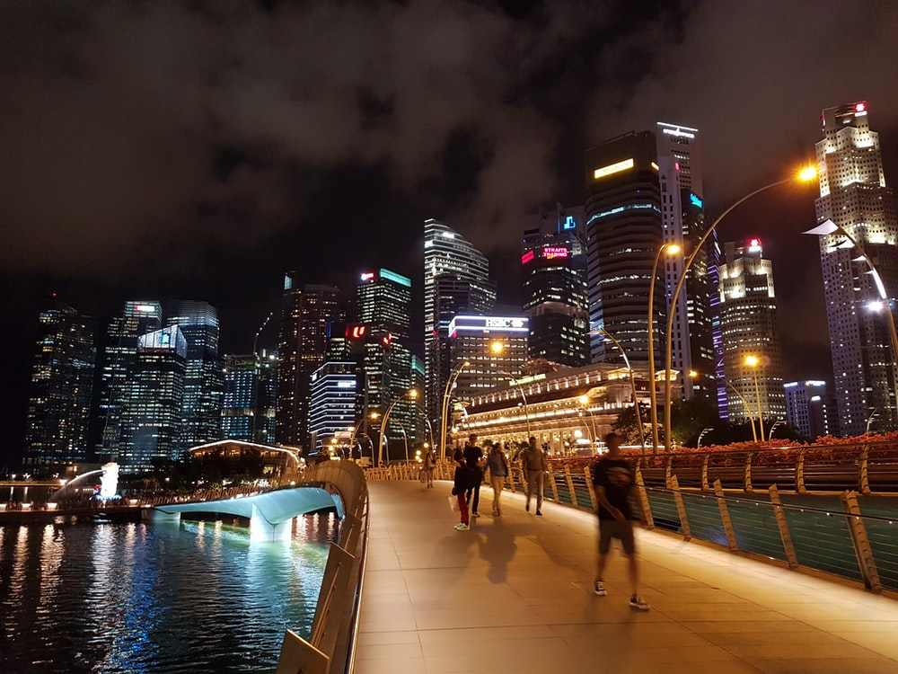 people walking on bridge over body of water during nighttime