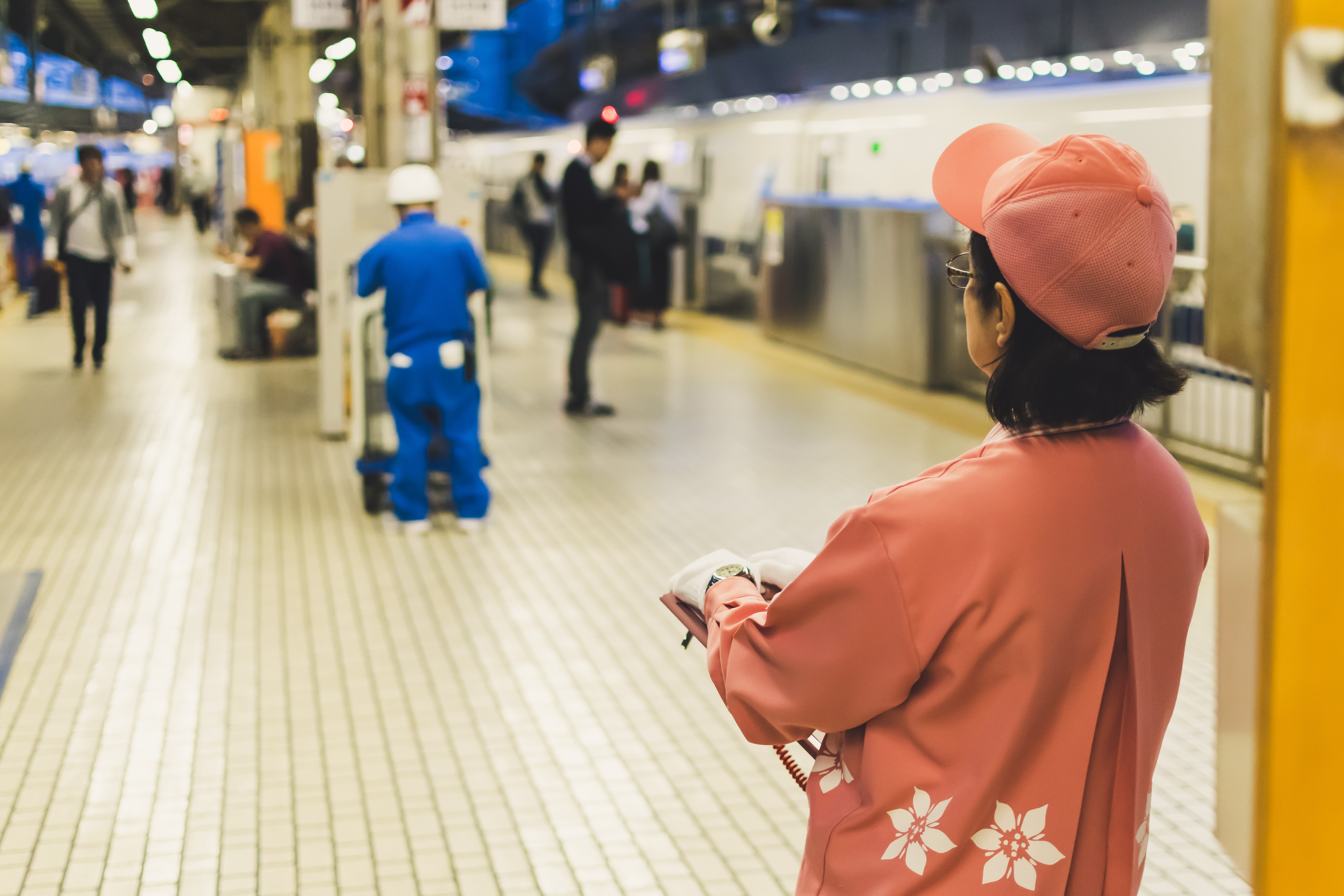 back of woman wearing fitted cap standing in train station