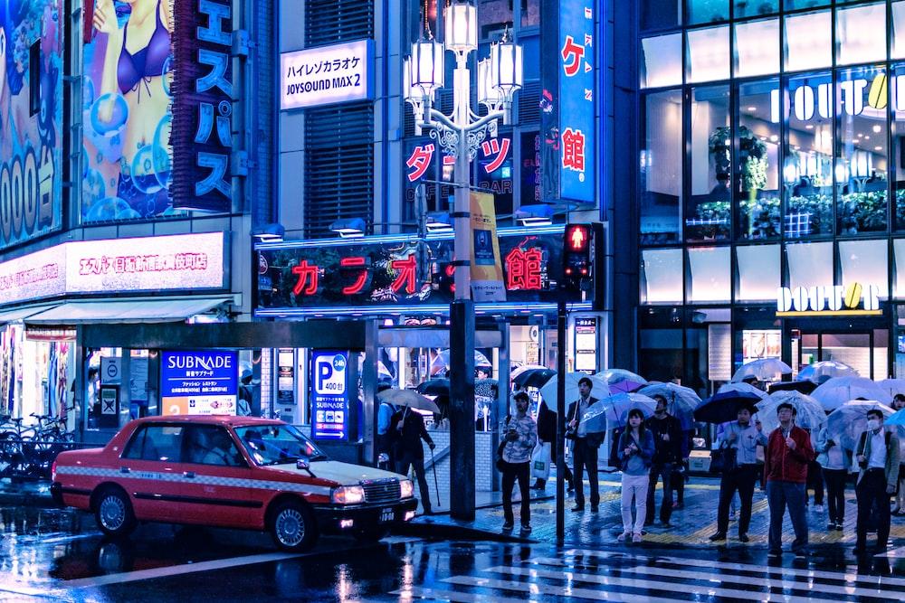 people holding umbrella standing near pedestrian lane