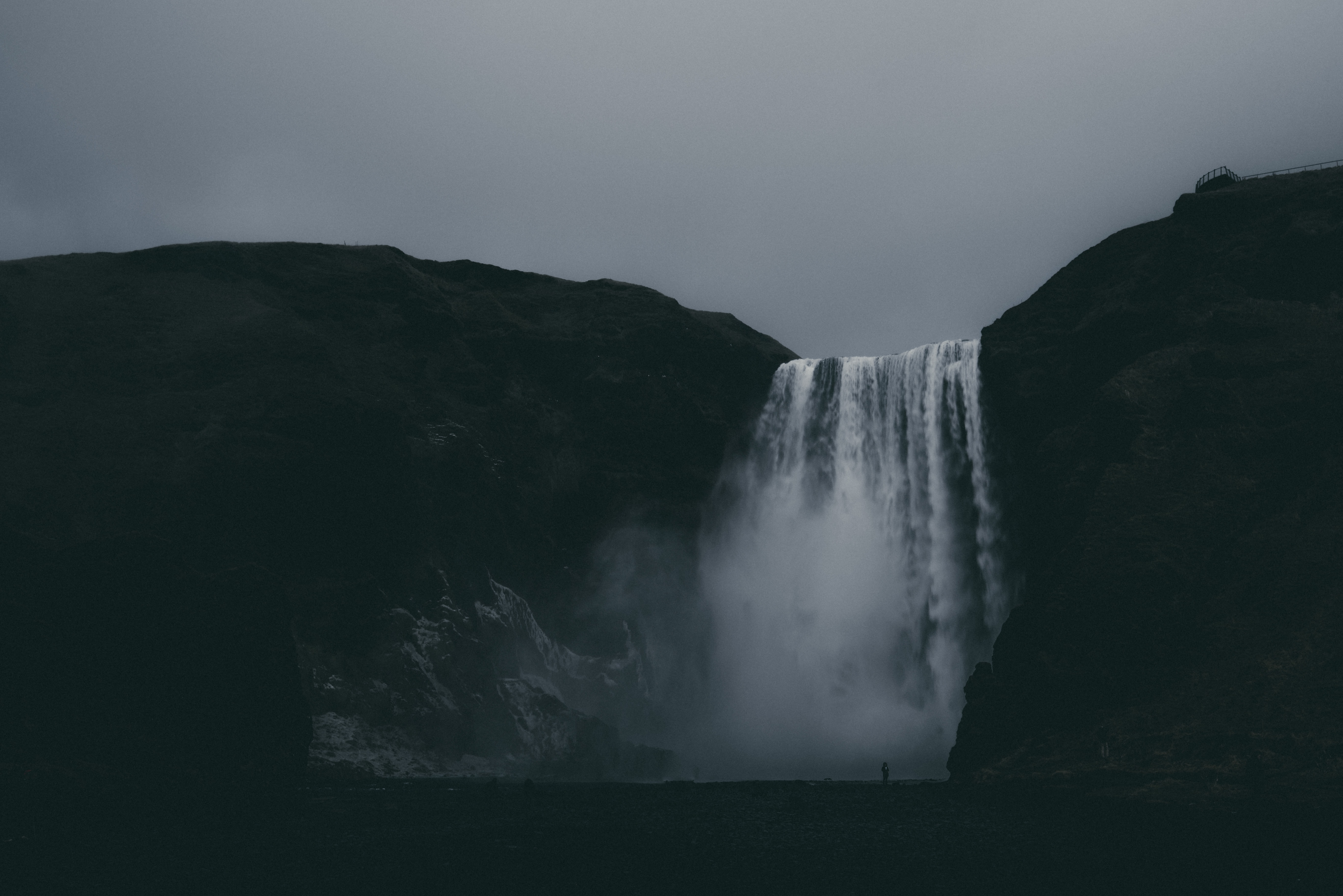 low-angle photography of waterfalls under cloudy sky
