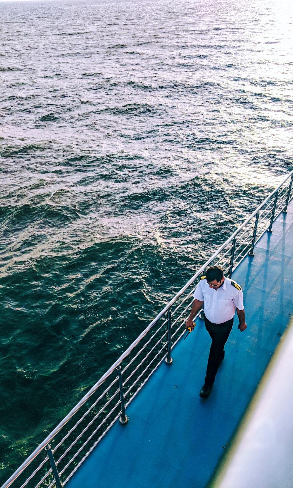 man walking on blue boat surface