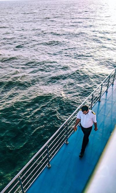 man walking on blue boat