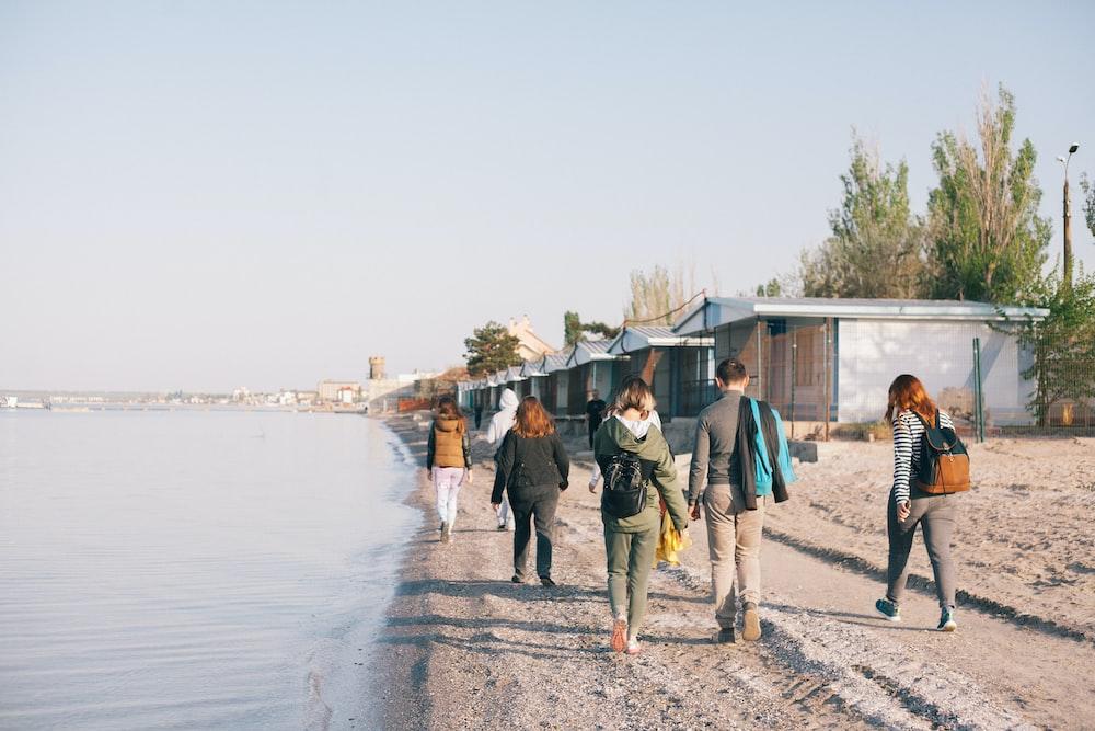 people walking beside seashore towards houses at daytime