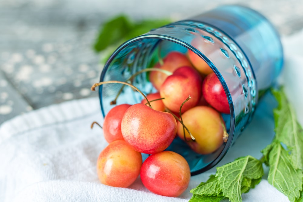bunch of cherry in drinking glass